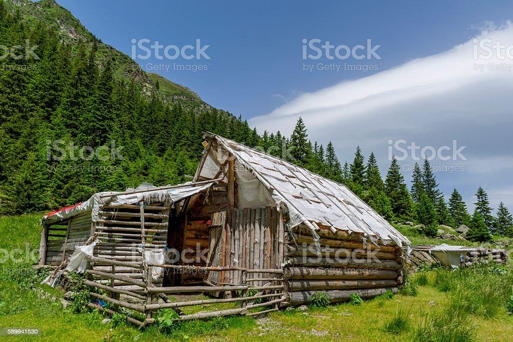 Abandoned wooden sheepfold near mountains range stock photo