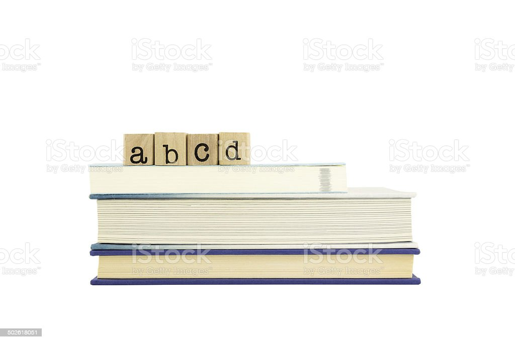 abcd word on wood stamps and books stock photo