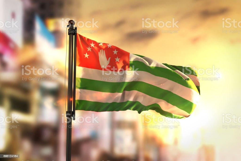 Abkhazia Flag Against City Blurred Background At Sunrise Backlight stock photo