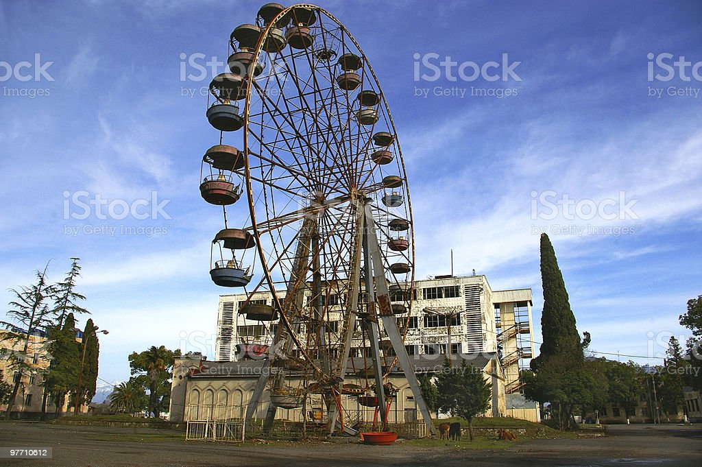 Abkhazia, rusty destroy ferris wheel  and war-ravaged spa-hotel background royalty-free stock photo