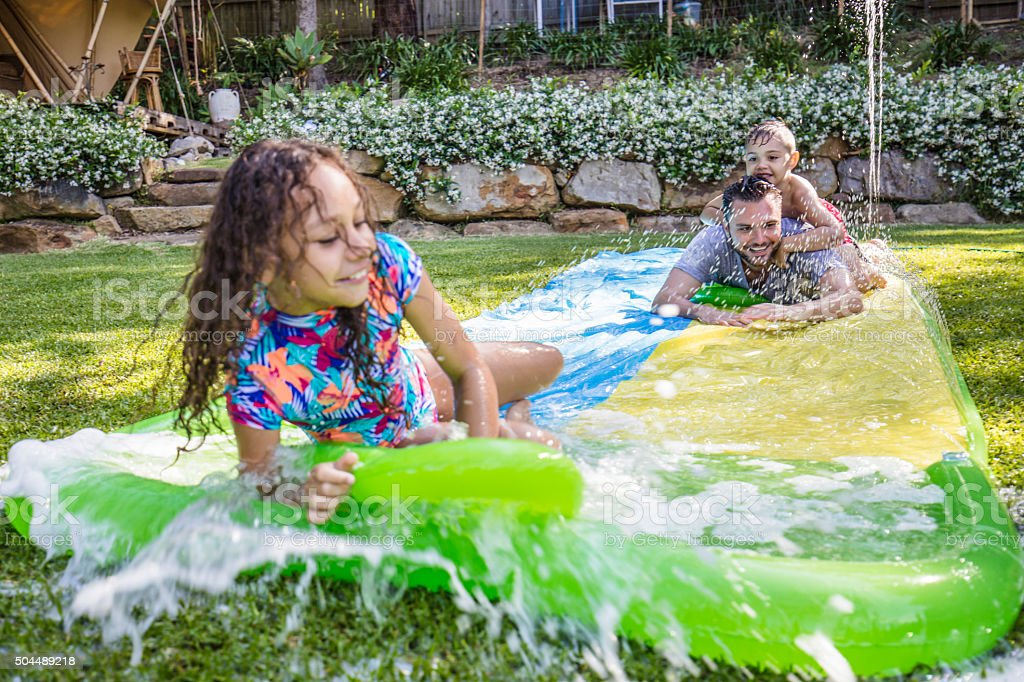Aboriginal children on slip 'n slide in the garden stock photo