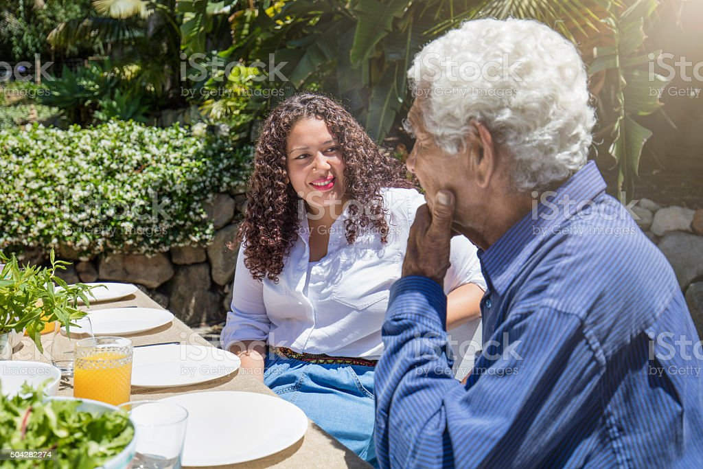 Aboriginal father talking with his daughter on a barbecue stock photo
