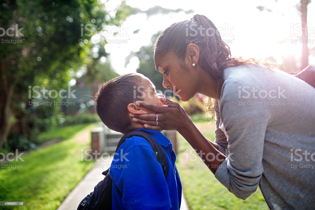Aboriginal Indigenous mother and school son saying goodbye stock photo