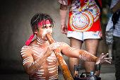 Aboriginal male playing didgeridoo, street performer, Australia, copy space, vignette