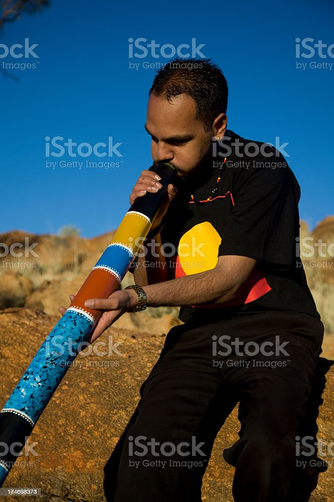 Aboriginal man playing a colorful didgeridoo stock photo