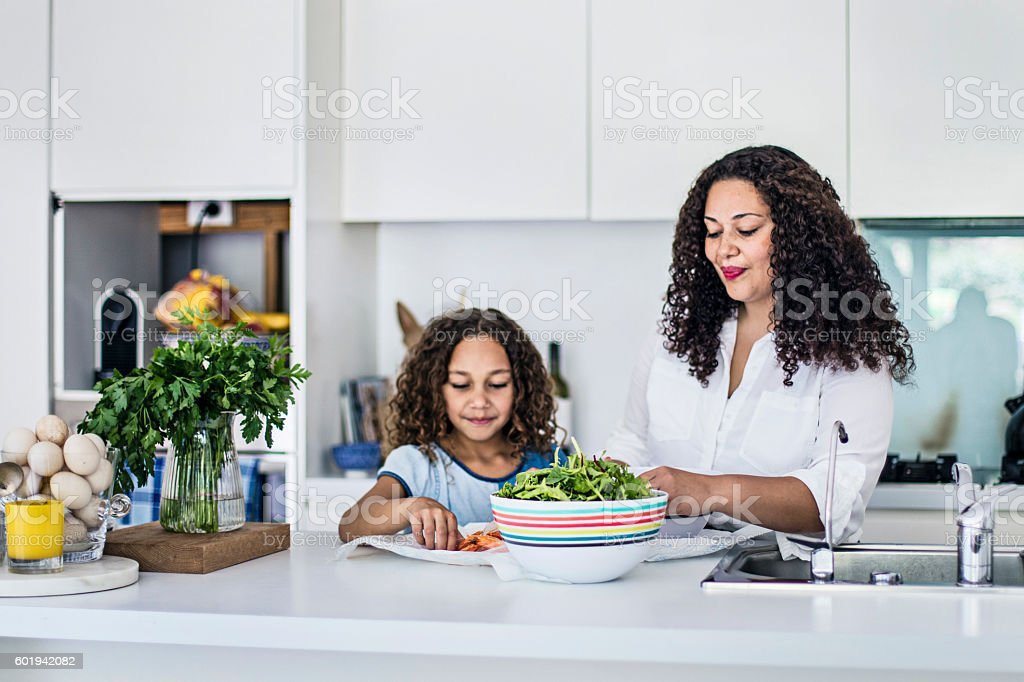 Aboriginal mother and daughter preparing a fresh salad stock photo