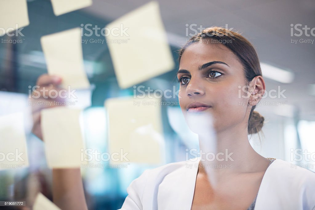 Aboriginal woman picking up an idea note fro the board stock photo