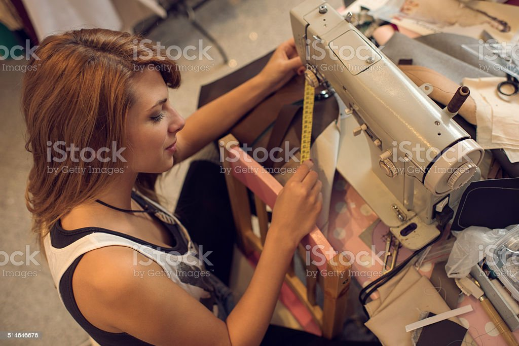 Above view of a fashion designer working on sewing machine. stock photo