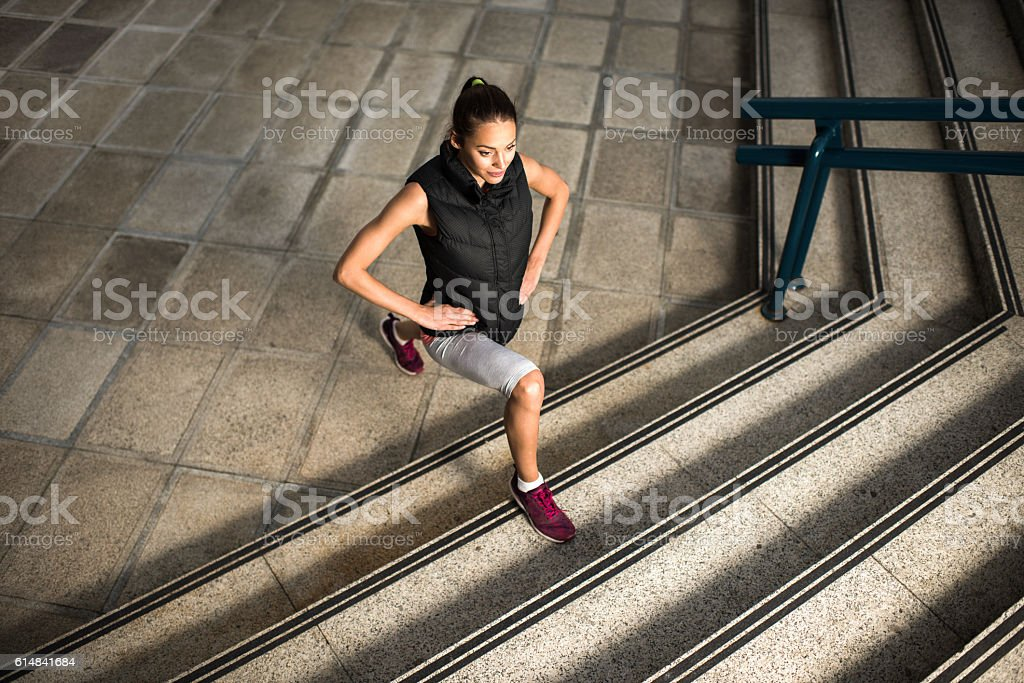 Above view of athletic woman exercising lunges on stairs. stock photo