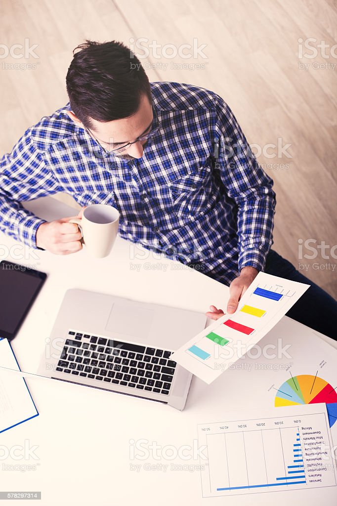 Above view of businessman analyzing diagrams in home office. stock photo