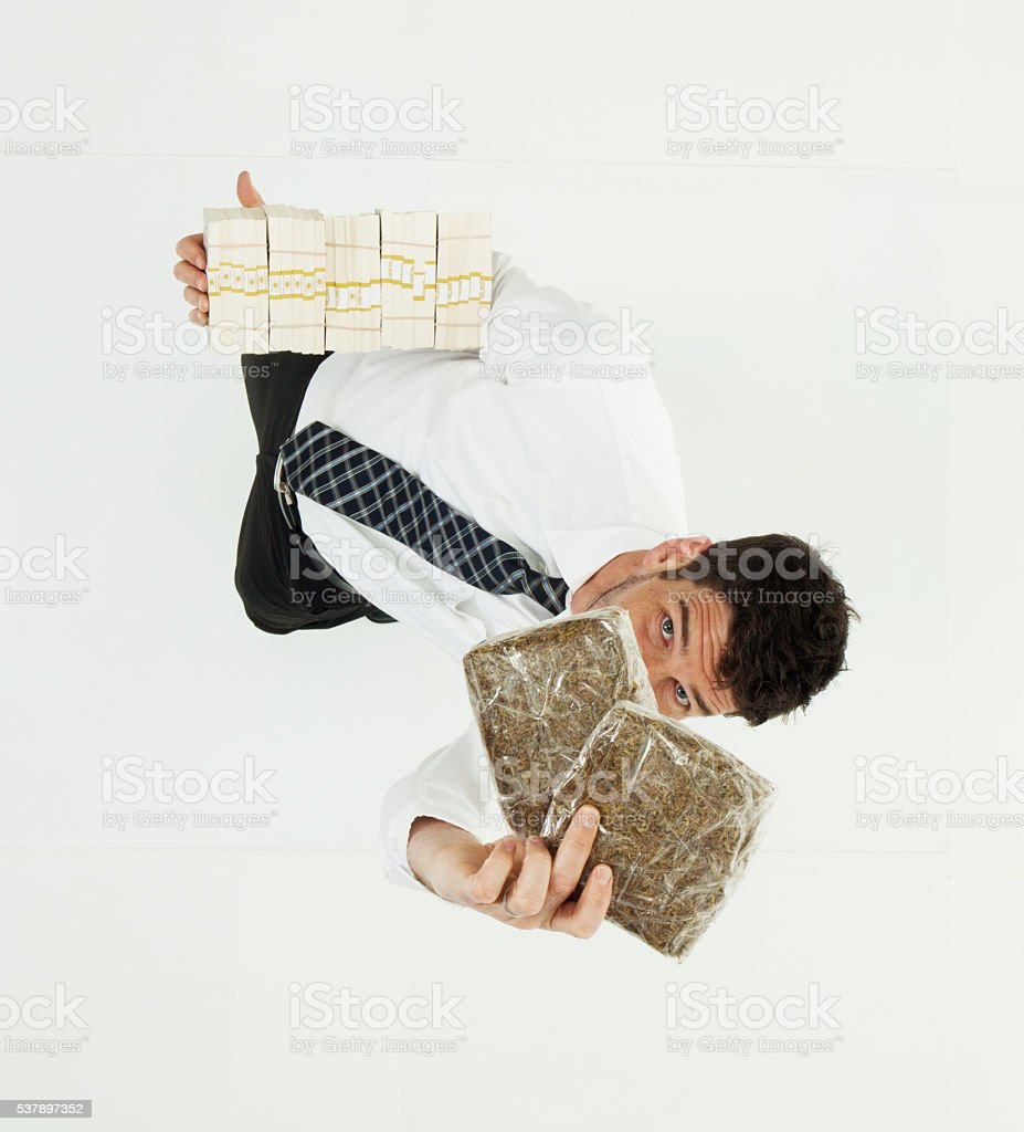 Above view of businessman holding money and drug stock photo
