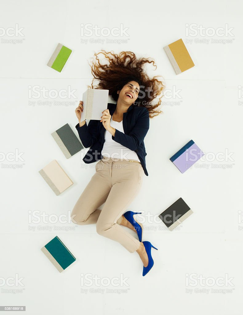 Above view of businesswoman lying with books stock photo