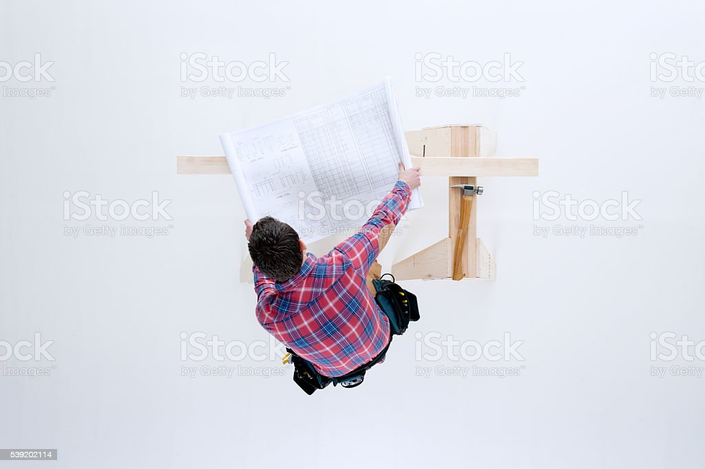 Above view of carpenter working with blue print stock photo