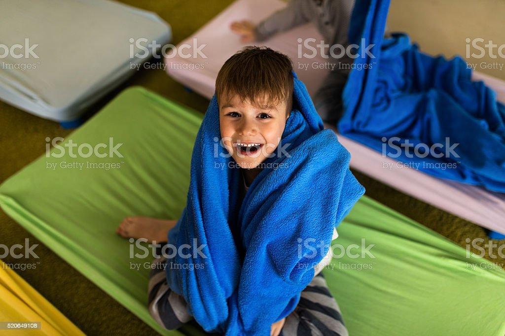 Above view of cheerful little boy in pajama in kindergarten. stock photo