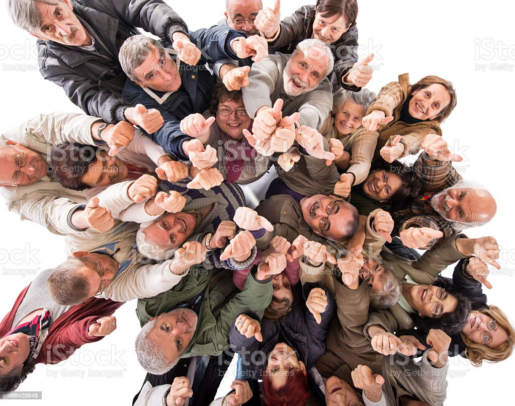 Above view of cheerful seniors showing thumbs up. stock photo