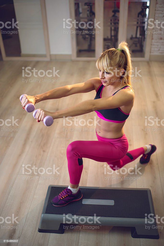 Above view of exercising step aerobics with dumbbells. stock photo
