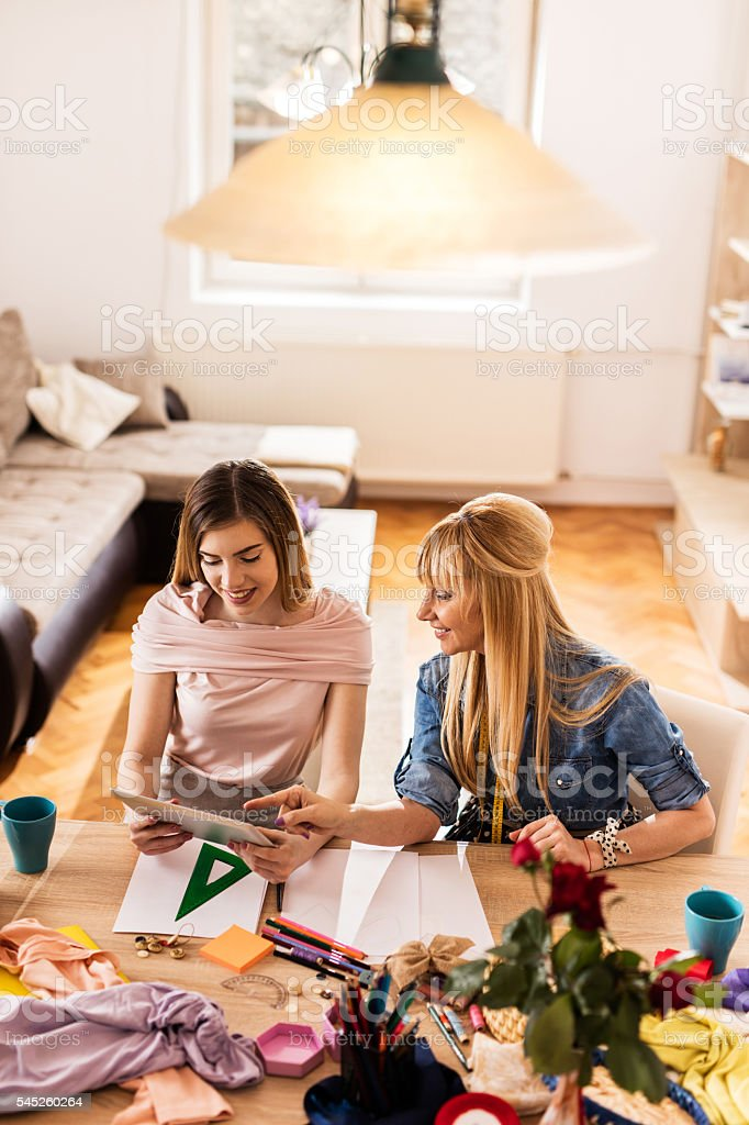 Above view of family fashion designers using touchpad together. stock photo