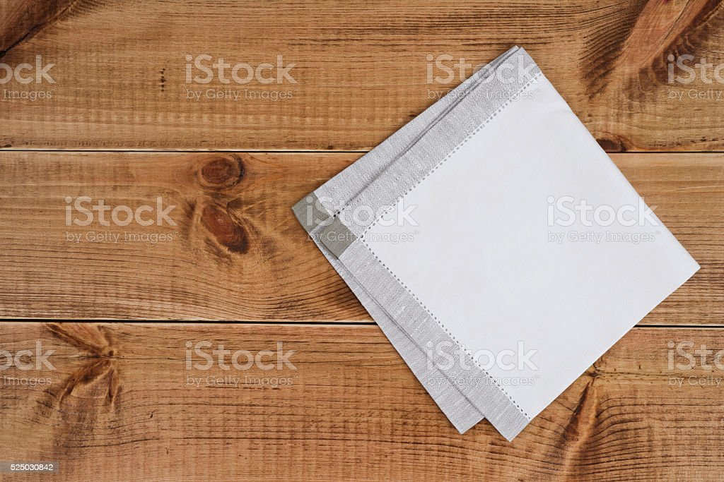 Above view of folded linen napking on wooden texture background stock photo