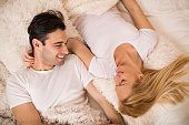 Above view of happy couple lying down in bed.