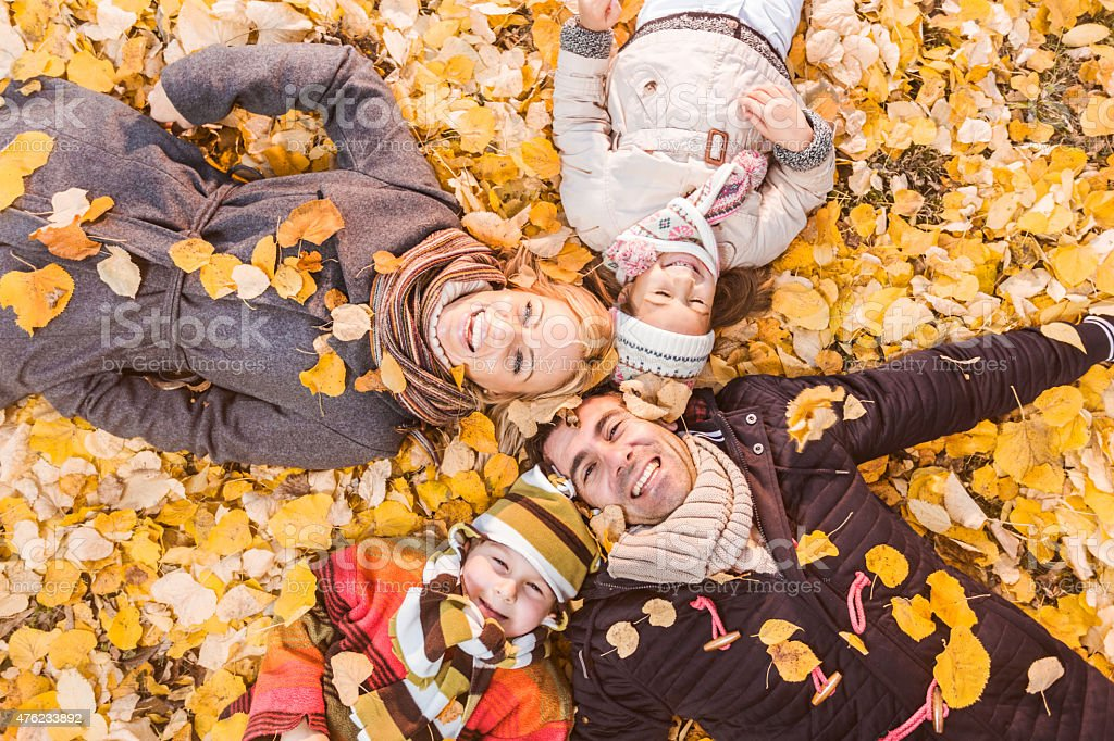 Above view of happy family lying in autumn leaves. stock photo