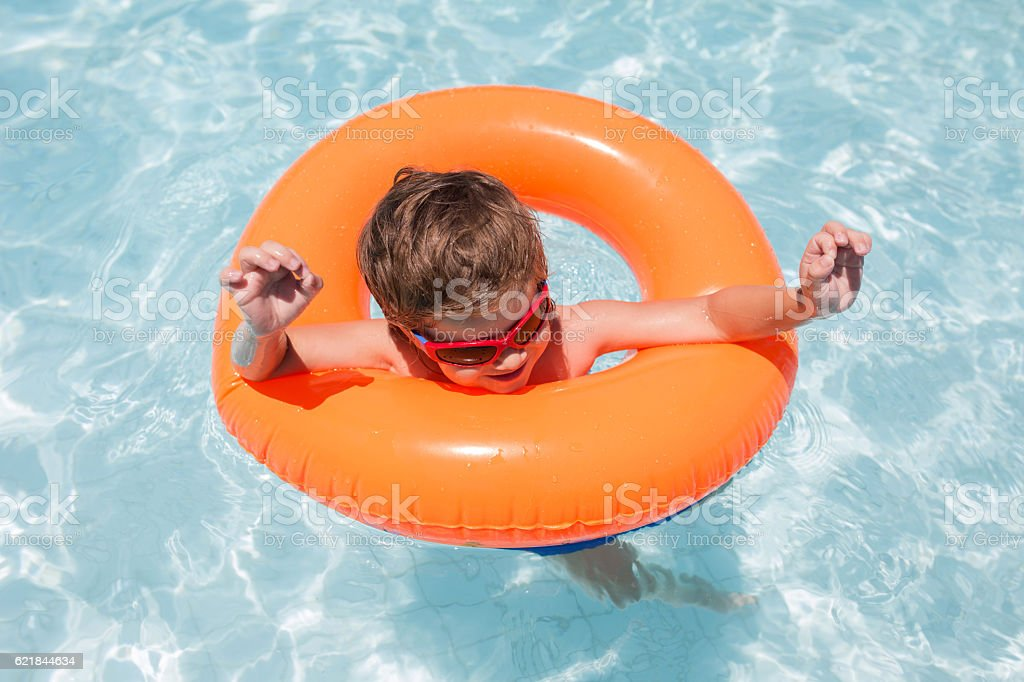 Above view of kid having fun in swimming pool. stock photo