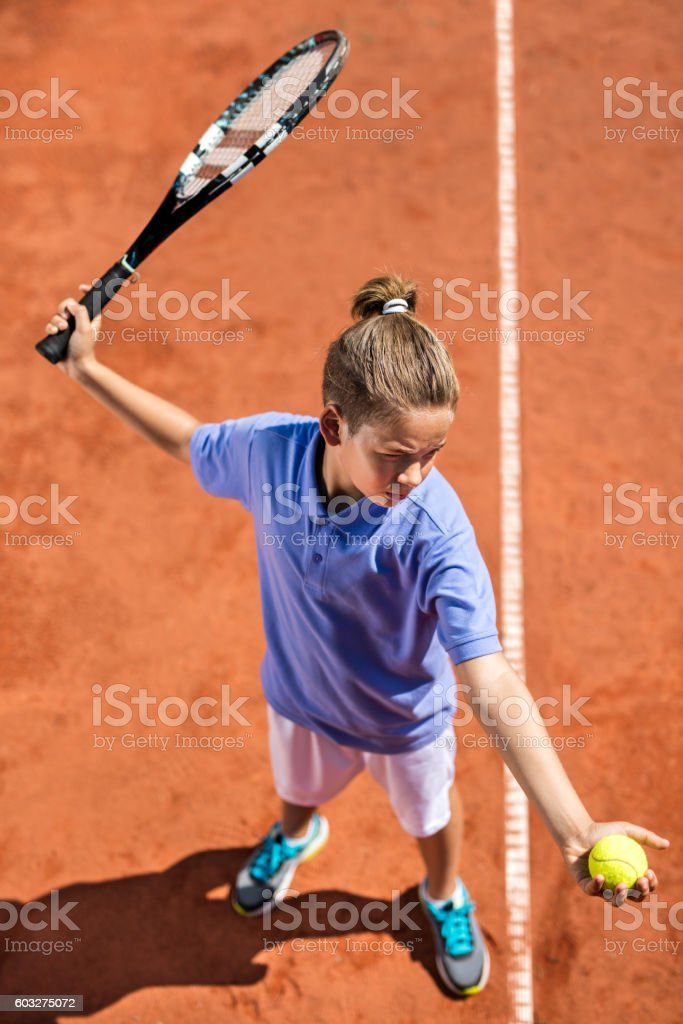 Above view of little boy serving a tennis ball. stock photo