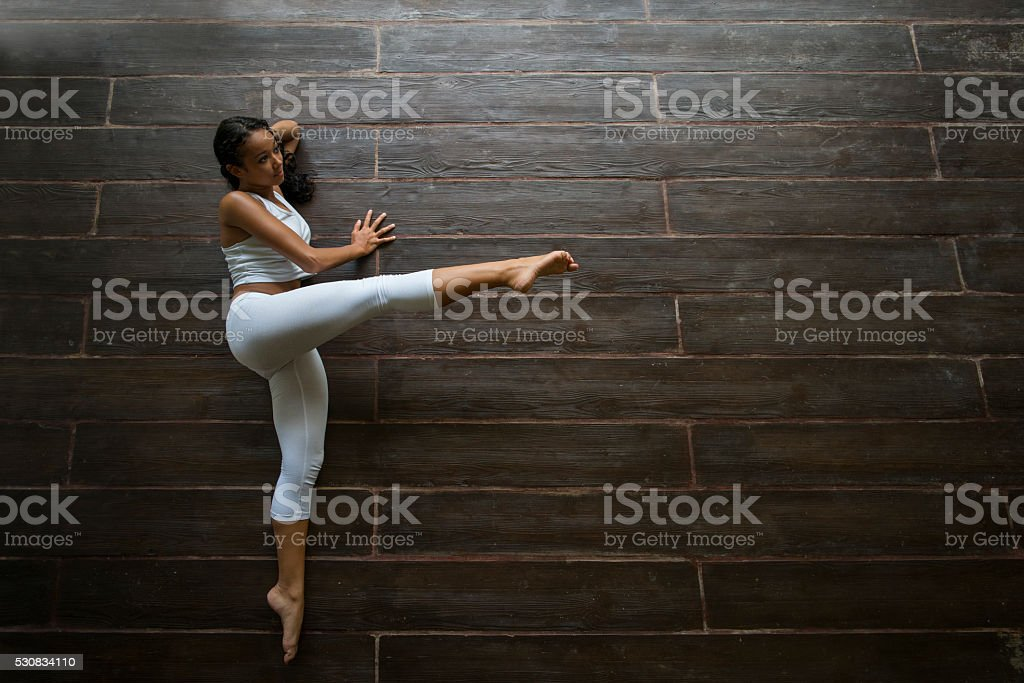 Above view of Malaysian athlete stretching on wooden floor. stock photo