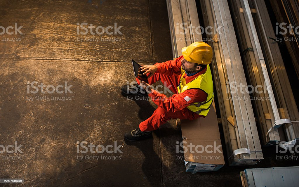 Above view of manual worker using touchpad in aluminum mill. stock photo