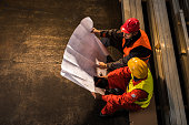 Above view of metal workers examining blueprints.