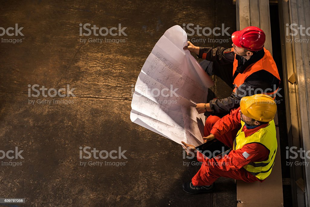 Above view of metal workers examining blueprints. stock photo