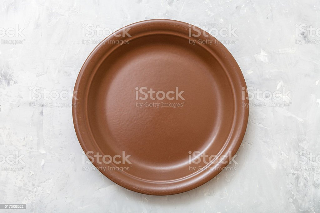 above view of one brown plate on gray concrete stock photo