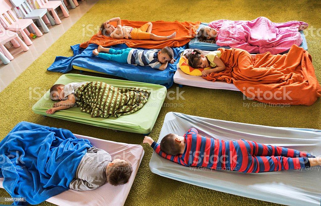 Above view of preschoolers in pajamas sleeping at kindergarten. stock photo