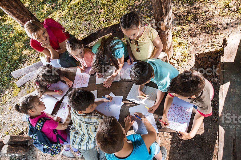 Above view of school children drawing on a field trip. stock photo