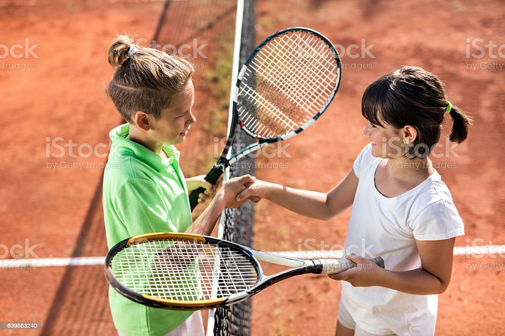 Above view of small tennis players shaking hands after match. stock photo