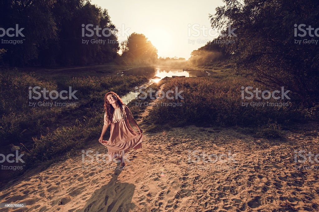 Above view of smiling woman taking a bow at sunset. stock photo