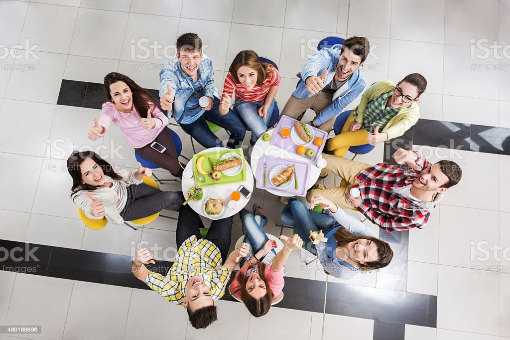 Above view of students showing thumbs up on lunch break. stock photo