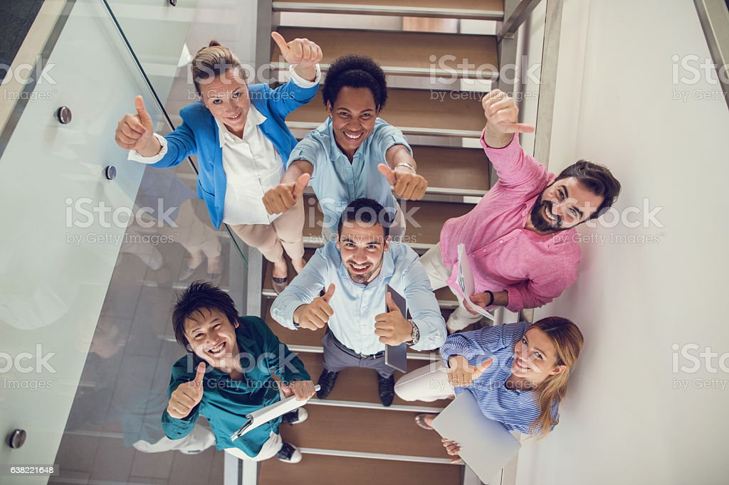 Above view of successful business team showing thumbs up. stock photo