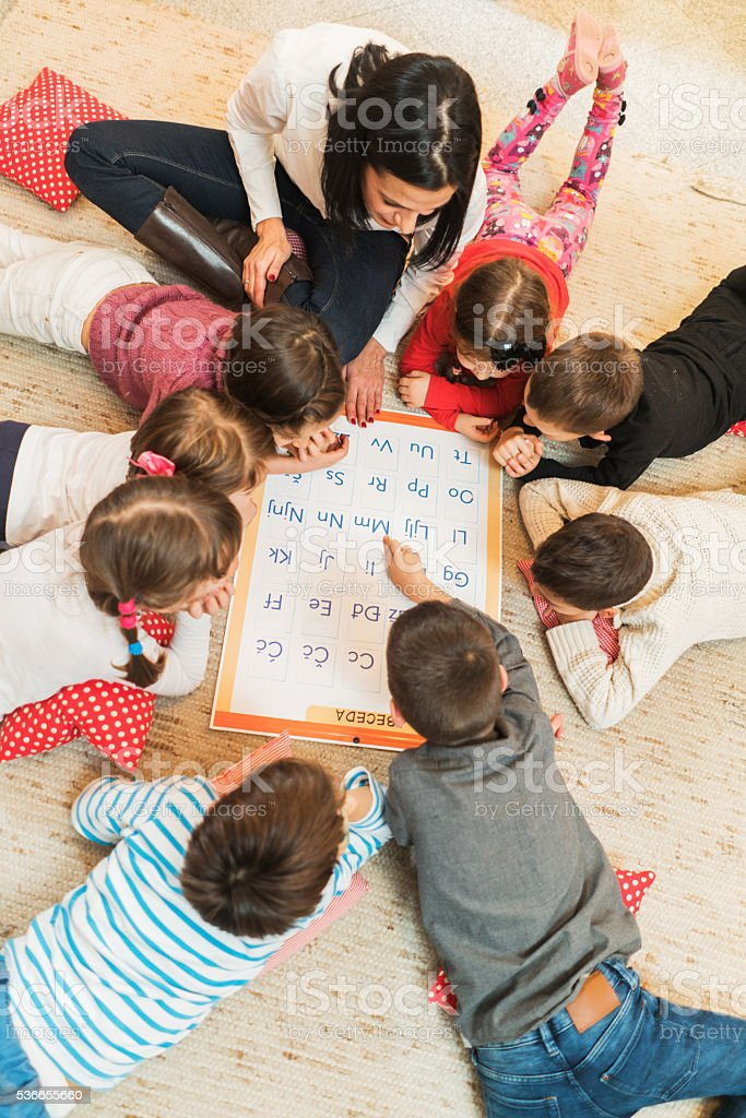 Above view of teacher and kids learning in preschool. stock photo