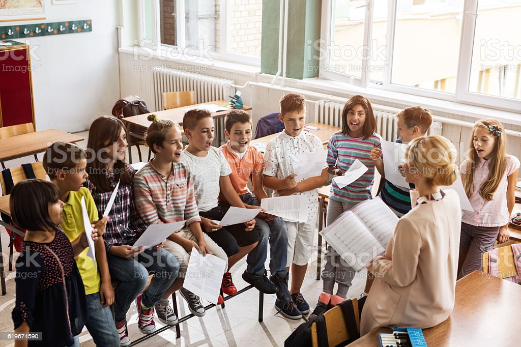 Above view of teacher singing with children during music lesson. stock photo