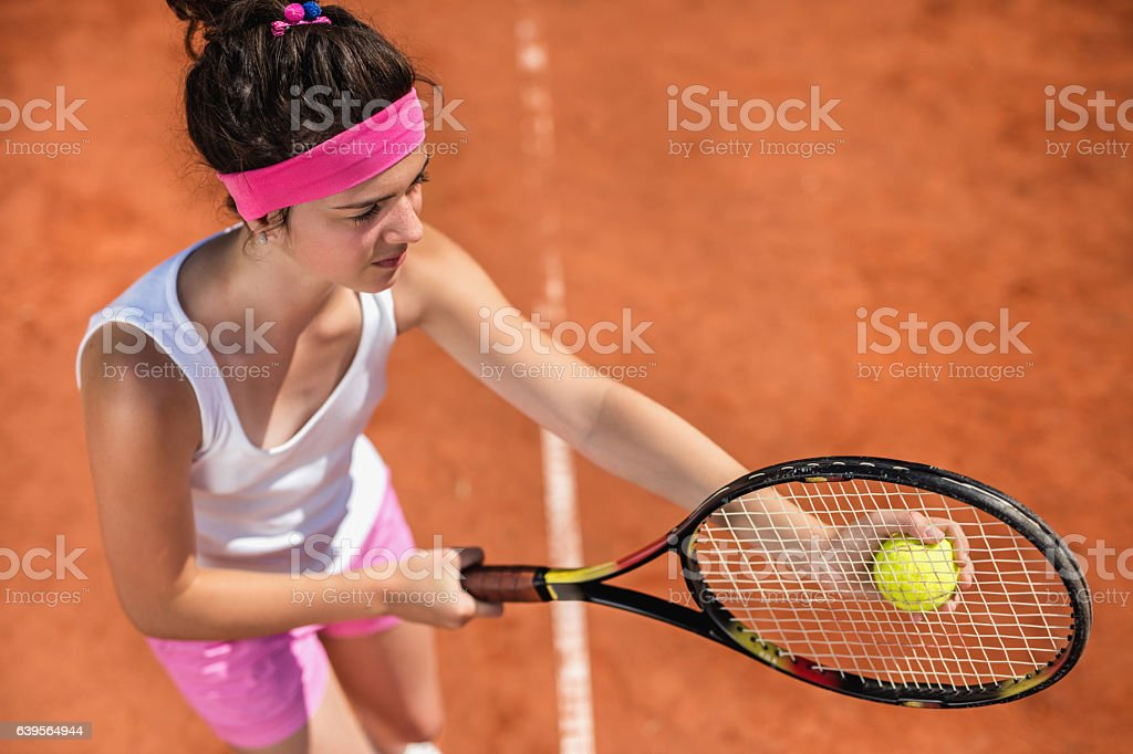 Above view of teenage girl serving tennis ball. stock photo