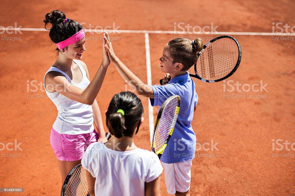 Above view of tennis players giving high five after match. stock photo
