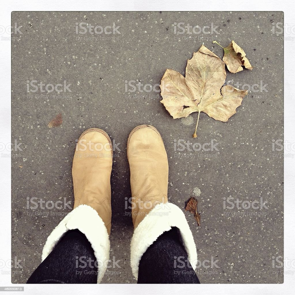 Above view of two feet in boots on cement with a fallen leaf stock photo
