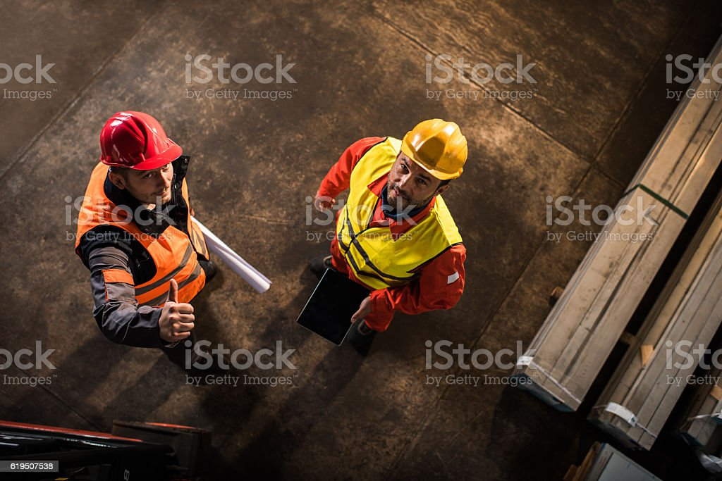 Above view of two workers standing in industrial building. stock photo
