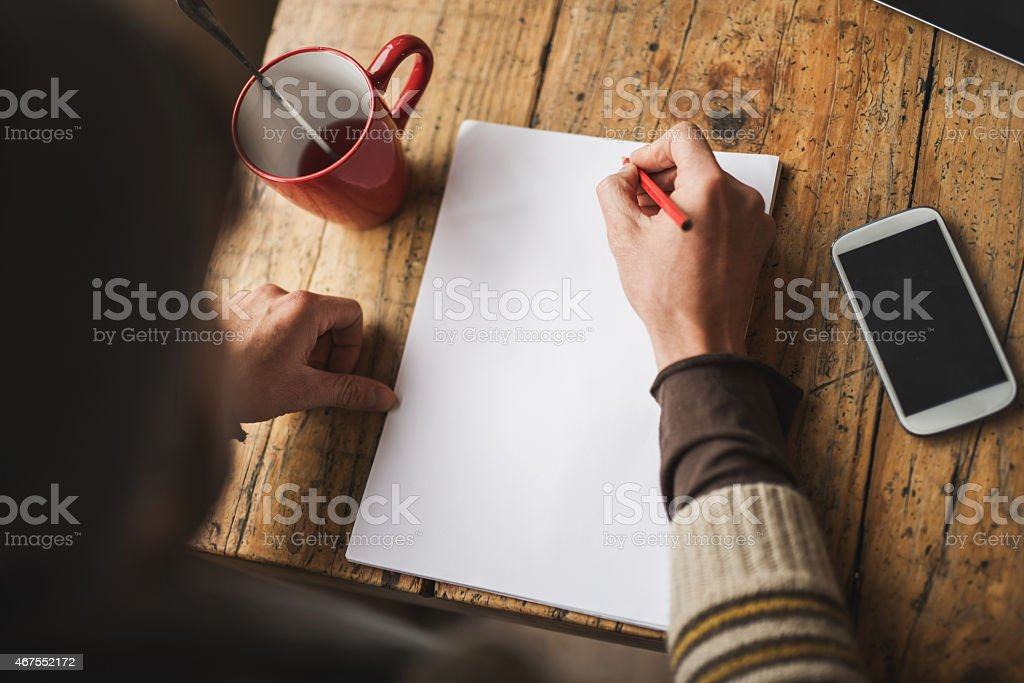 Above view of unrecognizable person writing on paper. Copy space stock photo