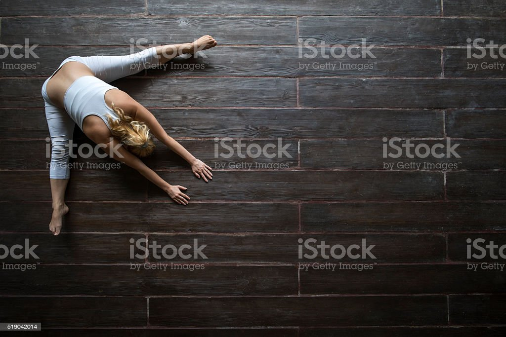 Above view of woman doing relaxation exercises on wooden floor. stock photo