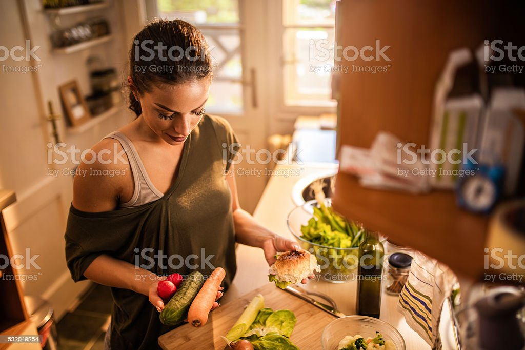 Above view of woman in kitchen with food in hands. stock photo