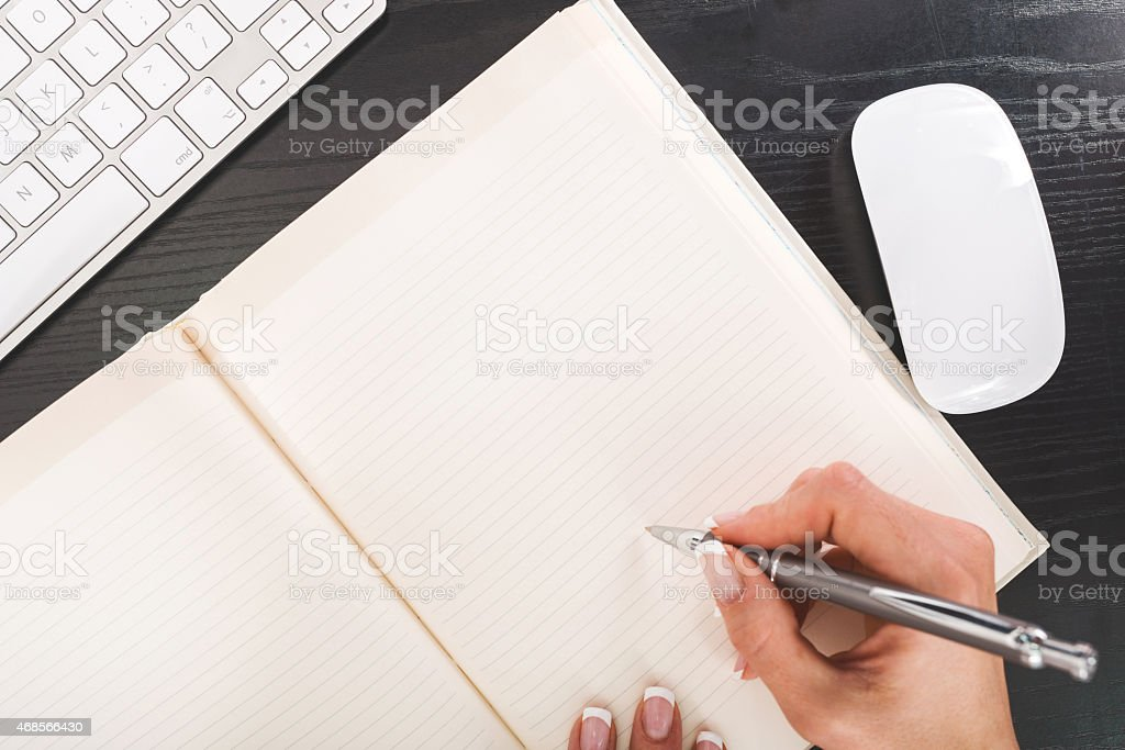 Above view of woman's hand writing. stock photo