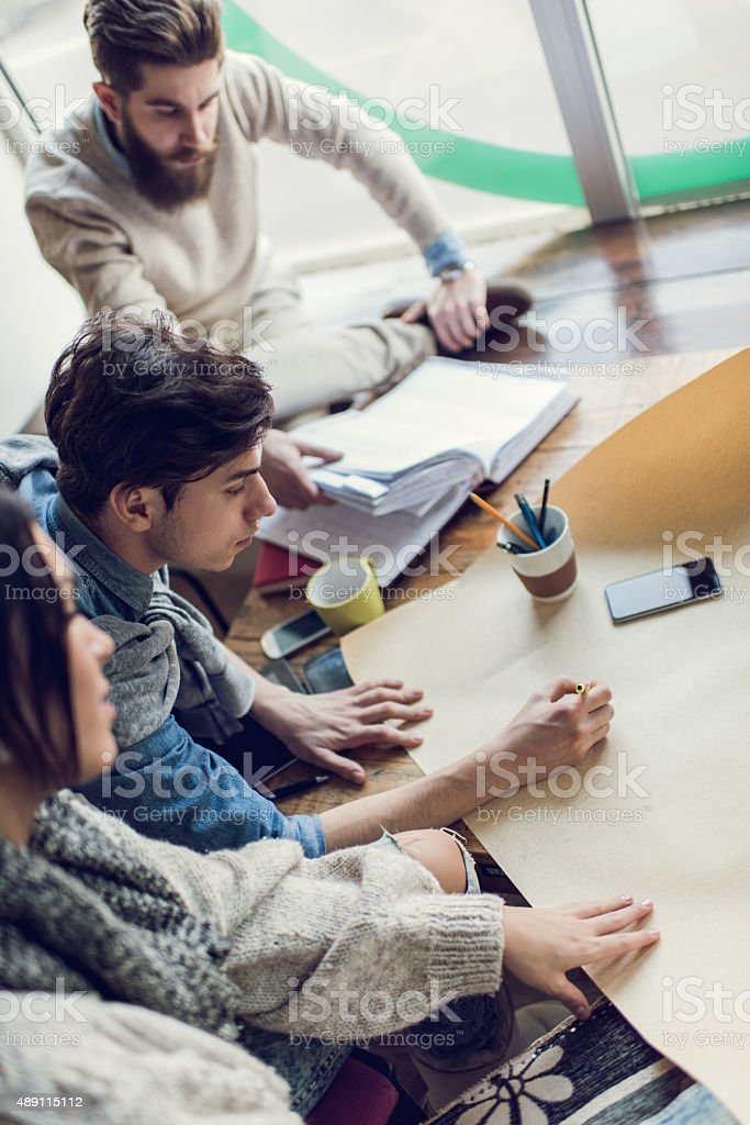 Above view of young architects drawing a new project. stock photo