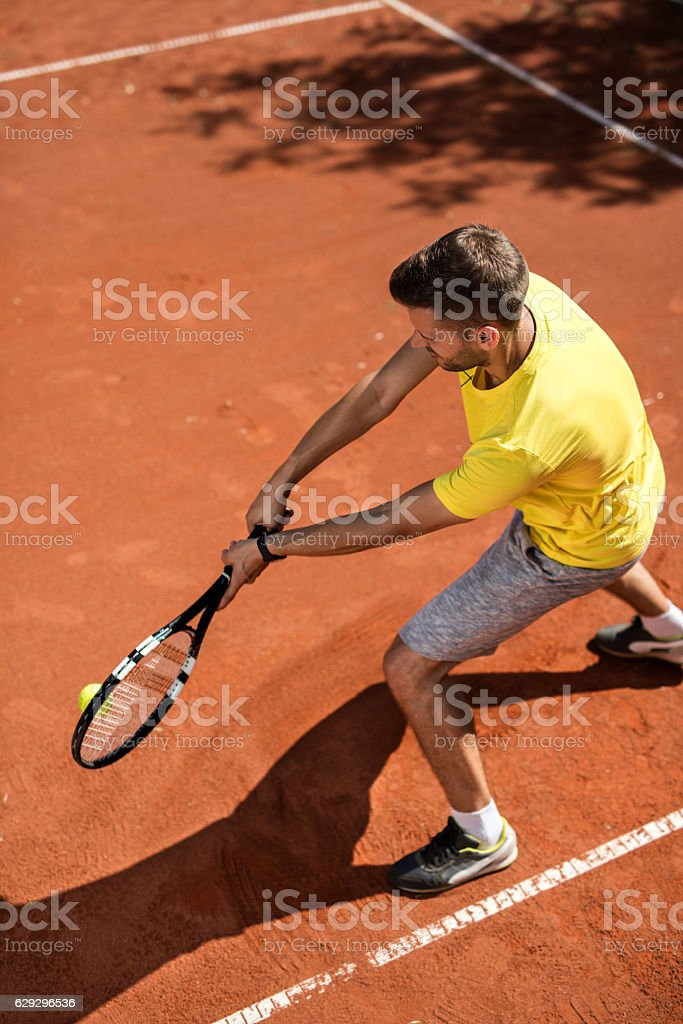 Above view of young man playing tennis on the court. stock photo