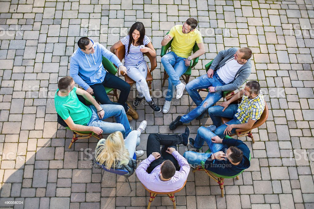 Above view of young people sitting in circle and talking. stock photo